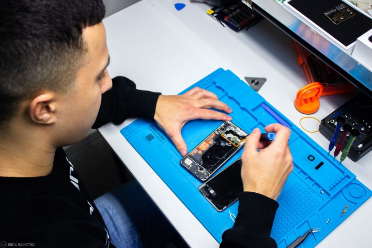 Ein Mitarbeiter repariert ein Handy bei einem Display-bruch